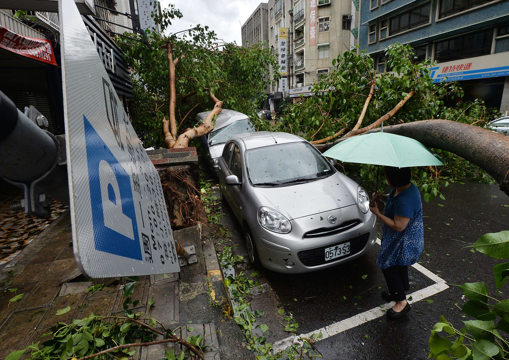 """. A woman views a vehicle damaged by fallen trees after Typhoon Soulik hit Taipei on July 13, 2013.  Thousands of people were evacuated in Taiwan and the entire island declared an \""""alert zone\"""" as Typhoon Soulik made landfall, killing one person and injuring seven. MARK RALSTON/AFP/Getty Images"""
