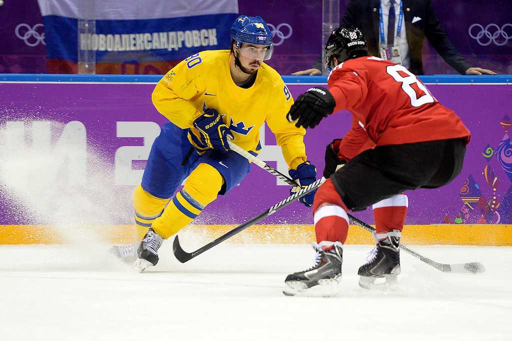 . Sweden\'s Marcon Johansson is defended by Switzerland\'s Kevin Romy during the action at Bolshoy Arena. Sochi 2014 Winter Olympics on Friday, February 14, 2014. (Photo by AAron Ontiveroz/The Denver Post)
