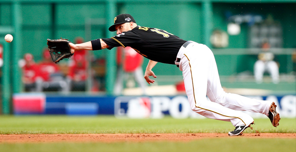 . Clint Barmes #12 of the Pittsburgh Pirates misses a ground ball hit by Matt Carpenter #13 of the St. Louis Cardinals during Game Four of the National League Division Series at PNC Park on October 7, 2013 in Pittsburgh, Pennsylvania.  (Photo by Jared Wickerham/Getty Images)