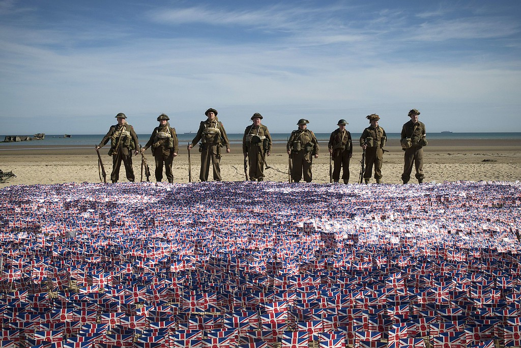 ". People wearing WWII British uniforms stand in front of 22.000 British national flags on June 6, 2014 in Asnelles, Normandy, during a ceremony on the ""Gold beach\"" where British troops landed on June 6, 1944 during the Operation Overlord.   AFP PHOTO / JOEL SAGET/AFP/Getty Images"