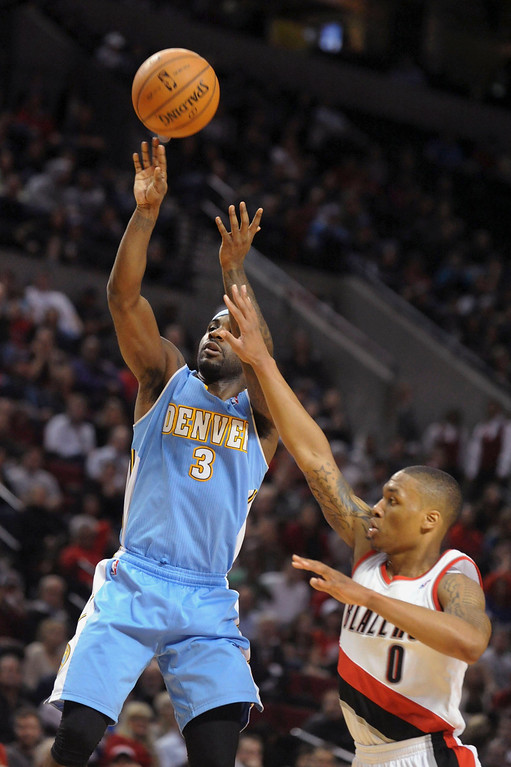 . Denver Nuggets point guard Ty Lawson (3) hits a jump shot over Portland Trail Blazers point guard Damian Lillard (0) during the fourth quarter of their NBA basketball game in Portland, Oregon, February 27, 2013. The Denver Nuggets won the game 111-109. REUTERS/Steve Dykes