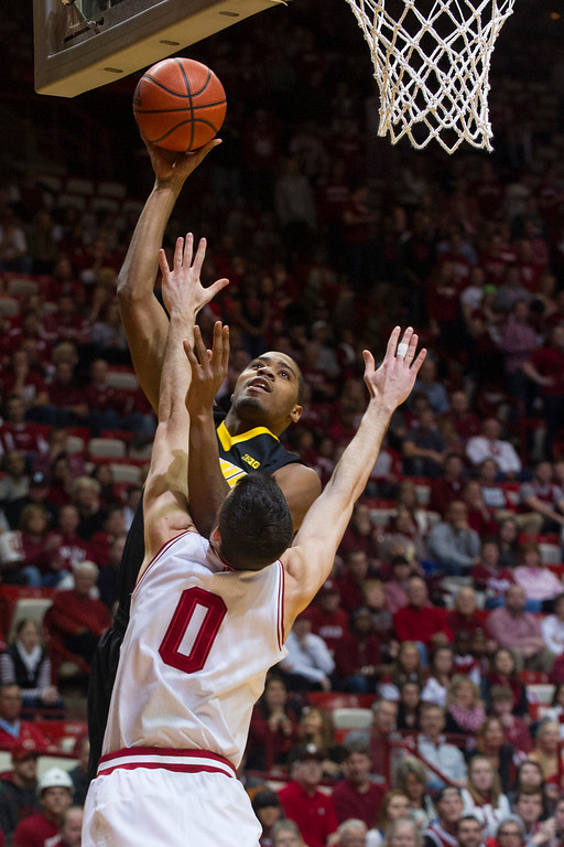 . Iowa\'s Melsahn Basabe, top, shoots over Indiana\'s Will Sheehey (0) in the first half of an NCAA college basketball game on Thursday, Feb. 27, 2014, in Bloomington, Ind. (AP Photo/Doug McSchooler)