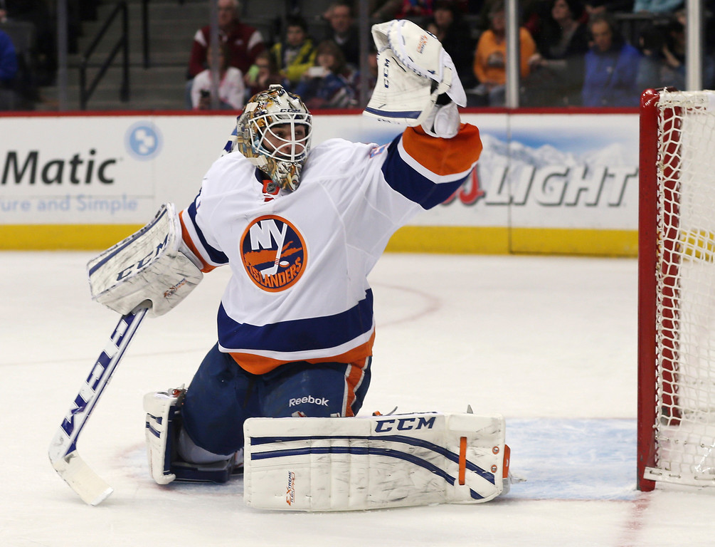 . New York Islanders goalie Kevin Poulin makes a glove save on a shot by the Colorado Avalanche during the first period of an NHL hockey game in Denver on Friday, Jan. 10, 2014. (AP Photo/David Zalubowski)
