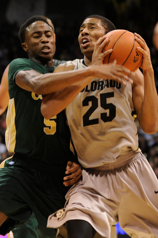 . Buffs point guard Spencer Dinwiddie (25) drove to the basket past CSU defender Jon Octeus (5) in the second half. The University of Colorado men\'s basketball team defeated Colorado State University 70-61 at the Coors Events Center Wednesday night, November 5, 2012. Karl Gehring/The Denver Post