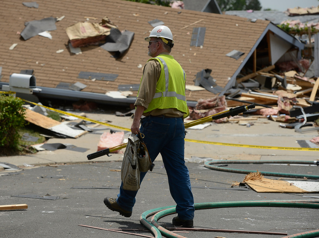 . An Xcel Energy worker steps over a fier hose at the scene of house explosion on the 9300 block of Ingalls Street in Westminster, Colorado, Thursday afternoon June 13, 2013.  (Photo By Andy Cross/The Denver Post)
