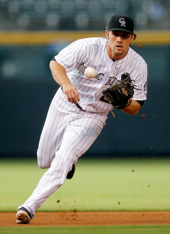 . Colorado Rockies shortstop Charlie Culberson grabs a ground ball hit by Cincinnati Reds\' Jay Bruce during the first inning of a baseball game Friday, Aug. 15, 2014, in Denver. Bruce was out at first. (AP Photo/Jack Dempsey)