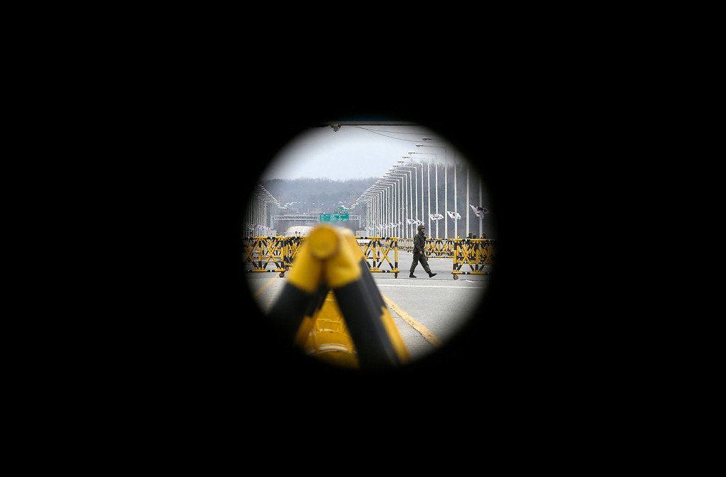 . A South Korean army soldier is seen through the barricade hole as he guards barricaded Unification Bridge near the border village of Panmunjom, which has separated the two Koreas since the Korean War, in Paju, north of Seoul, South Korea, Monday, April 15, 2013. Oblivious to international tensions over a possible North Korean missile launch, Pyongyang residents spilled into the streets Monday to celebrate a major national holiday, the birthday of their first leader, Kim Il Sung. (AP Photo/Lee Jin-man)