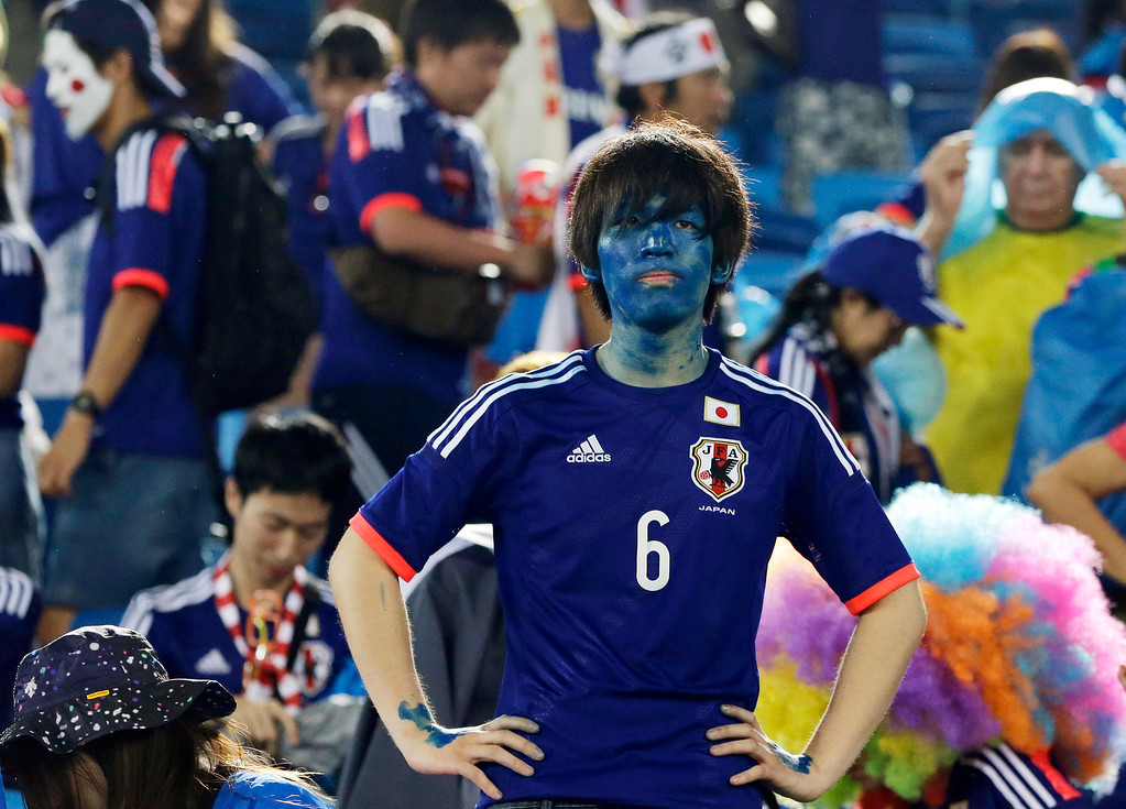 . A Japanese fan watches as players leave the field following their 0-0 tie with Greece during the group C World Cup soccer match between Japan and Greece at the Arena das Dunas in Natal, Brazil, Thursday, June 19, 2014.  (AP Photo/Shuji Kajiyama)