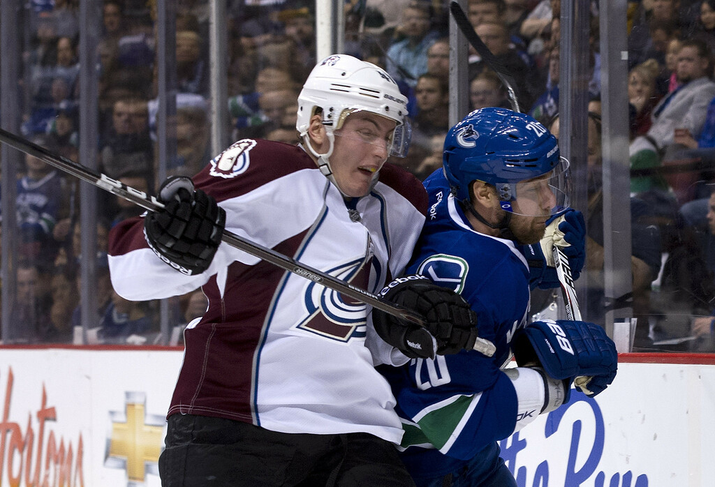 . VANCOUVER, CANADA - JANUARY 30: Tyson Barrie #41 of the Colorado Avalanche and Chris Higgins #20 of the Vancouver Canucks battle behind the net during the second period in NHL action on January 30, 2013 at Rogers Arena in Vancouver, British Columbia, Canada.  (Photo by Rich Lam/Getty Images)