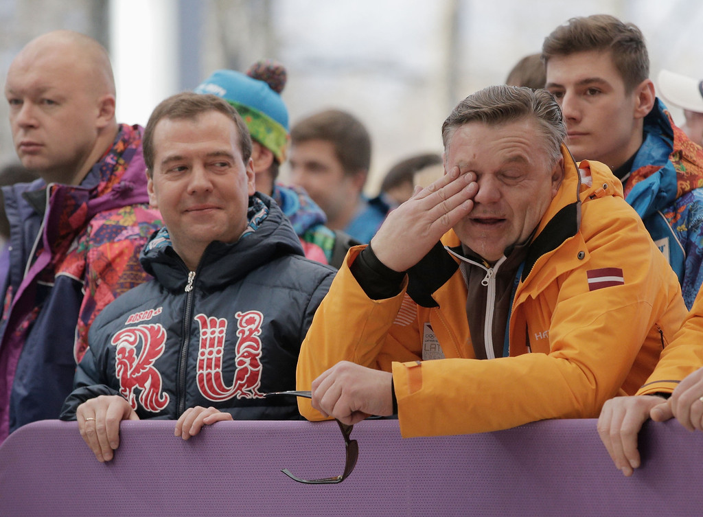 . Russian Prime Minister Dmitry Medvedev (L) and Latvia Bobsleigh team coach Zintis Ekmanis speak during the Men\'s Four-Man Bobsleigh on Day 16 of the Sochi 2014 Winter Olympics at Sliding Center Sanki on February 23, 2014 in Sochi, Russia.  (Photo by Adam Pretty/Getty Images)