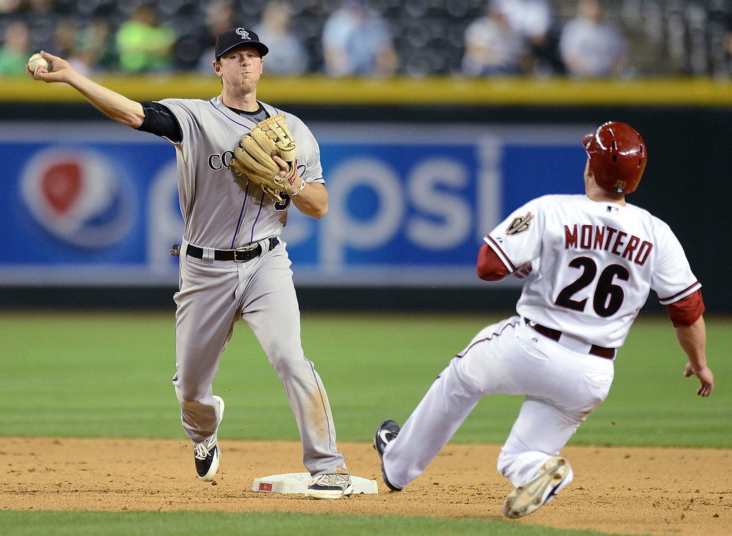 . DJ LeMahieu #9 of the Colorado Rockies turns a double play as Miguel Montero #26 of the Arizona Diamondbacks slides into second base in the seventh inning at Chase Field on April 28, 2014 in Phoenix, Arizona.  (Photo by Norm Hall/Getty Images)