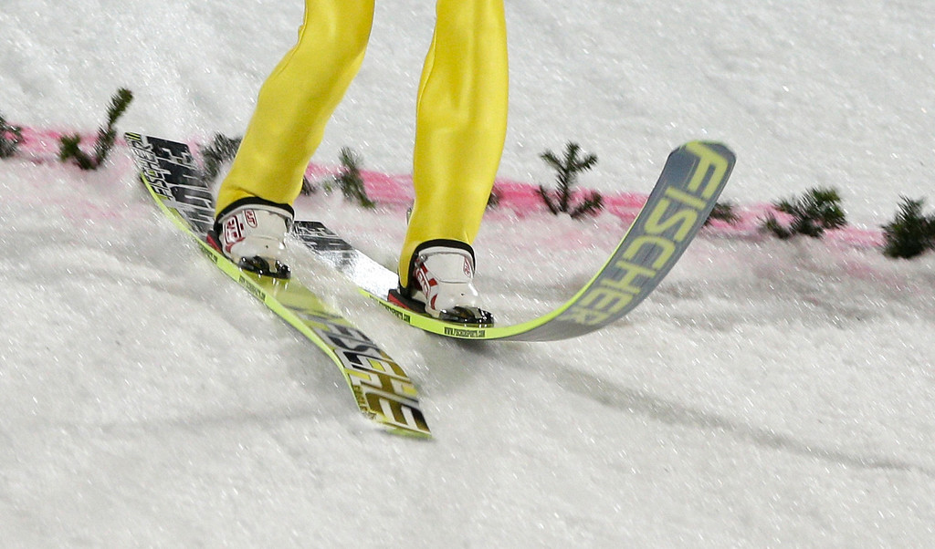 . The skis of Norway\'s Rune Velta bend as he lands his trial jump during the ski jumping large hill team competition at the 2014 Winter Olympics, Monday, Feb. 17, 2014, in Krasnaya Polyana, Russia. (AP Photo/Matthias Schrader)