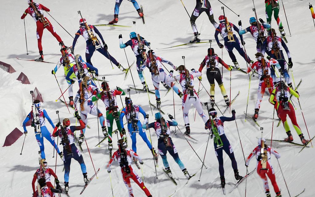 . The athletes starts for the women\'s biathlon 12.5k mass-start, at the 2014 Winter Olympics, Monday, Feb. 17, 2014, in Krasnaya Polyana, Russia. (AP Photo/Gero Breloer)