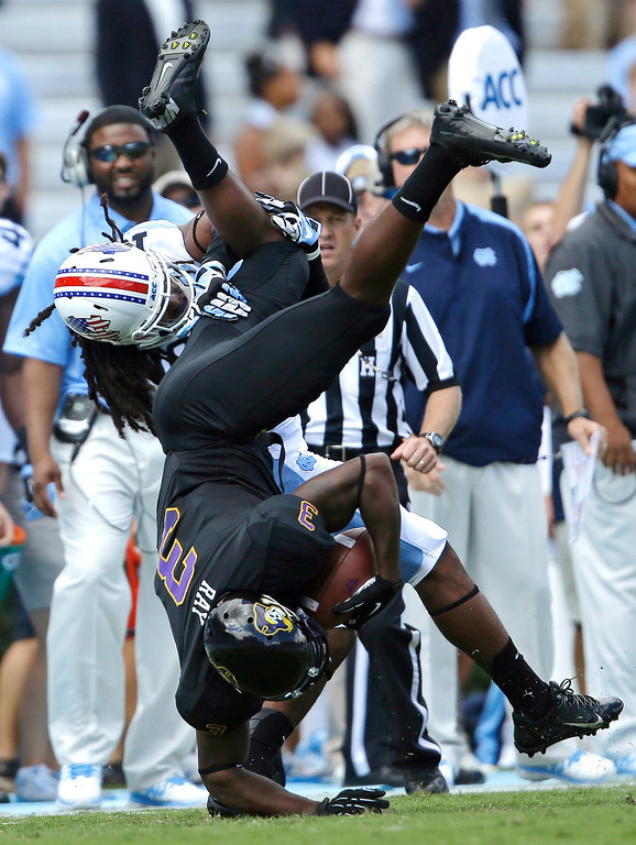 . East Carolina\'s Lance Ray (3) is upended by North Carolina\'s Tre Boston following a pass reception in the first half of an NCAA college football game in Chapel Hill, N.C., Saturday, Sept. 28, 2013. (AP Photo/Gerry Broome)