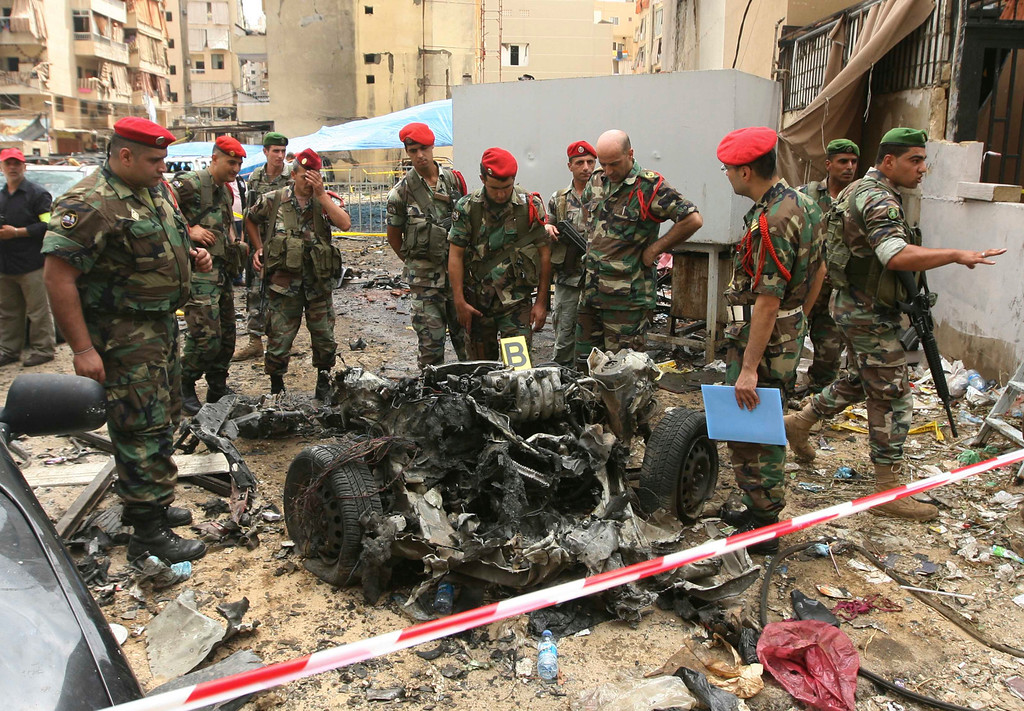 . Lebanese military police inspect the remains of a vehicle, at the site of an explosion in Beirut\'s southern suburbs, July 9, 2013.REUTERS/Hasan Shaaban