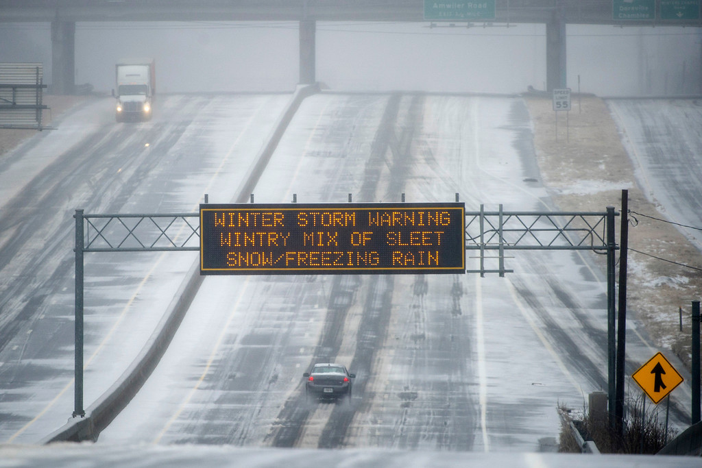 . A Georgia DOT sign warns drivers of winter weather as they travel a bleak section of Hwy. 141 on Wednesday, Feb. 12, 2014, in Norcross, Ga. The scene is the opposite of what drivers experienced two weeks ago when every major artery of metropolitan Atlanta was clogged during the last winter storm. (AP Photo/John Amis)