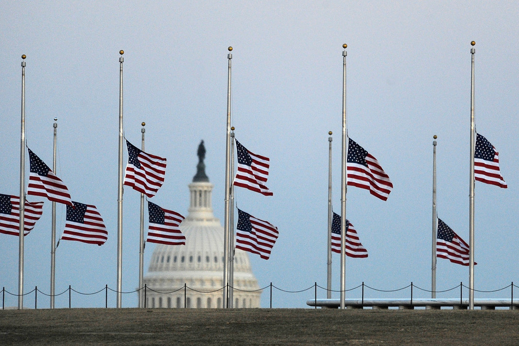 . The US Capitol dome is shown in the background as flags fly at half staff in honor of the victims of the shooting in Arizona that injured US Representative Gabrielle Giffords (D-AZ), at the Washington Monument in Washington January 9, 2011.    REUTERS/Jonathan Ernst