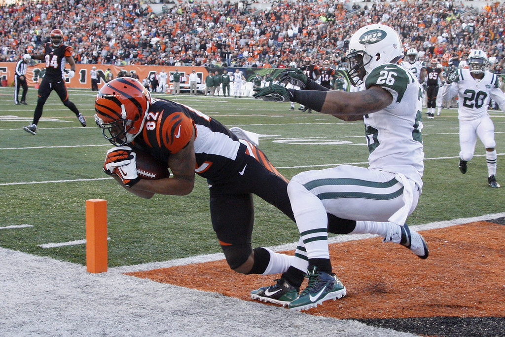 . Marvin Jones #82 of the Cincinnati Bengals hauls in a touchdown pass in front of Dawan Landry #26 of the New York Jets during their game at Paul Brown Stadium on October 27, 2013 in Cincinnati, Ohio.  The Bengals defeated the Jets 49-9.  (Photo by John Grieshop/Getty Images)