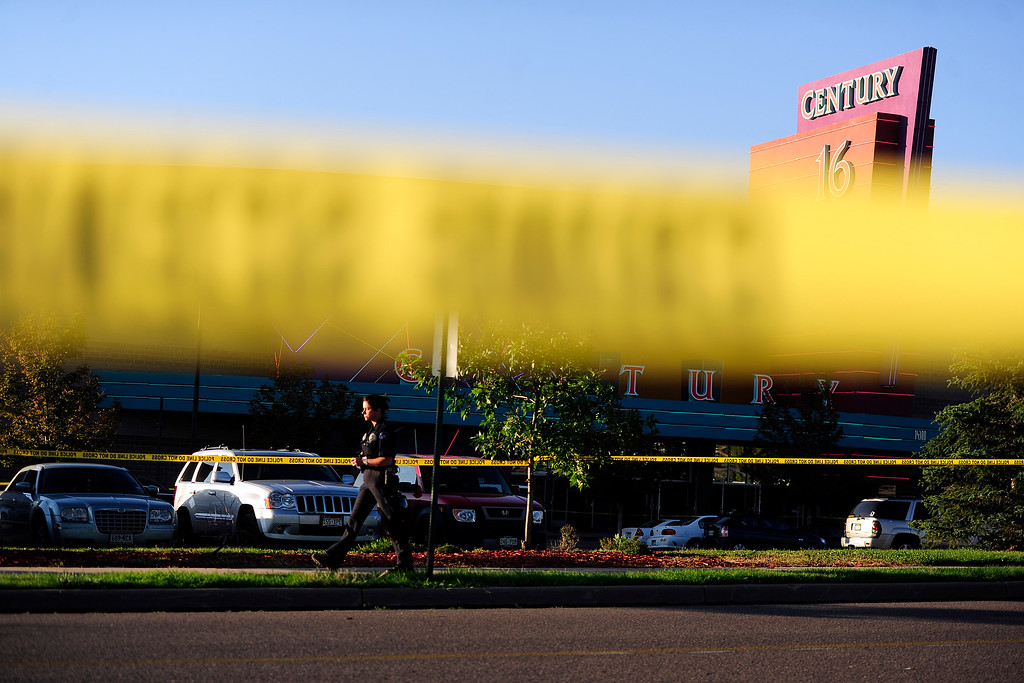 . An officer walks past the crime scene after a shooting left 12 people dead and dozens of others wounded at The Dark Knight Rises premiere at the Century Aurora 16 theater in Aurora on Friday, July 20, 2012. James Holmes, 24, is in custody after he surrendered to authorities early Friday morning following a shooting spree. AAron Ontiveroz, The Denver Post