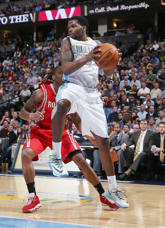 . Denver Nuggets guard Aaron Brooks, front, pulls in a loose ball in front of Houston Rockets guard Isaiah Canaan in the first quarter of an NBA basketball game in Denver on Wednesday, April 9, 2014. (AP Photo/David Zalubowski)
