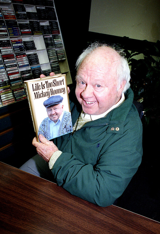 """. Mickey Rooney holds his autobiography, \""""Life Is Too Short,\"""" during a book signing at a bookstore in New York City on April 1, 1991.  Rooney, 70, has been married eight times, appeared on Broadway and has made 150 films.  (AP Photo/David Cantor)"""