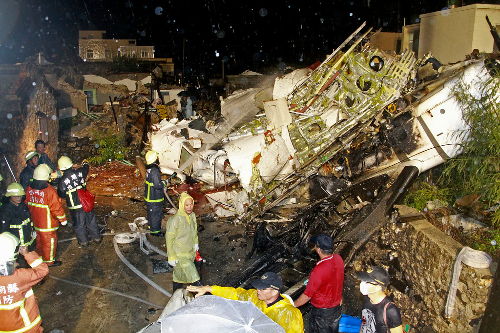 . Rescue workers work next to the wreckage of TransAsia Airways flight GE222 which crashed while attempting to land in stormy weather on the Taiwanese island of Penghu, late Wednesday, July 23, 2014. (AP Photo/Wong Yao-wen)
