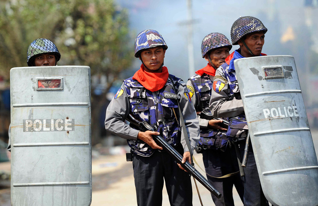 . Policemen stand guard in a street in riot-hit Meiktila, central Myanmar on March 22, 2013.  AFP PHOTO/ Soe Than WIN/AFP/Getty Images