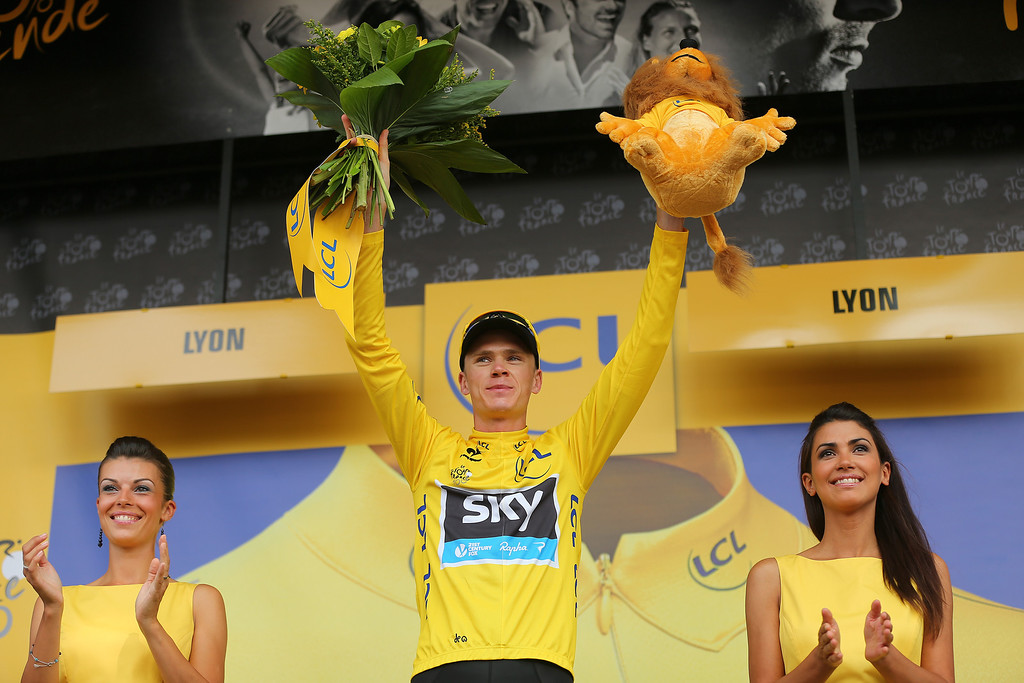 . LYON, FRANCE - JULY 13:  Current race leader and wearer of the Maillot Jaune, Chris Froome of Great Britain and SKY Procycling (C) celebrates on the podium after stage fourteen of the 2013 Tour de France, a 191KM road stage from Saint-Pourcain-sur-Sioule to Lyon, on July 13, 2013 in Lyon, France.  (Photo by Bryn Lennon/Getty Images)