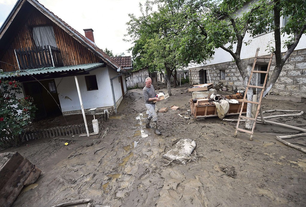 . A man walk on mud as he carries personal belongings out from his flooded house in Krupanj, some 130 kilometers south west of Belgrade, on May 20, 2014, after it was hit with floods and landslides, cutting the western Serbian town off for four days. Serbia declared three days of national mourning on May 20 as the death toll from the worst flood to hit the Balkans in living memory rose and health officials warned of a possible epidemic.    AFP PHOTO / ANDREJ ISAKOVIC/AFP/Getty Images