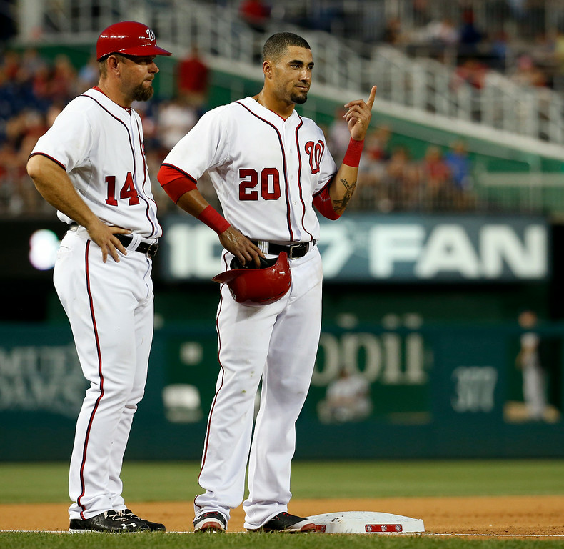 . Washington Nationals shortstop Ian Desmond (20) stands on third base with third base coach Bob Henley (14), as they wait for the umpires to review a ball hit by Desmond during the seventh inning of a baseball game against the Colorado Rockies at Nationals Park, Wednesday, July 2, 2014, in Washington. Desmond\'s hit was ruled a home run. The Nationals won 4-3, and swept the three-game series with the Rockies. (AP Photo/Alex Brandon)
