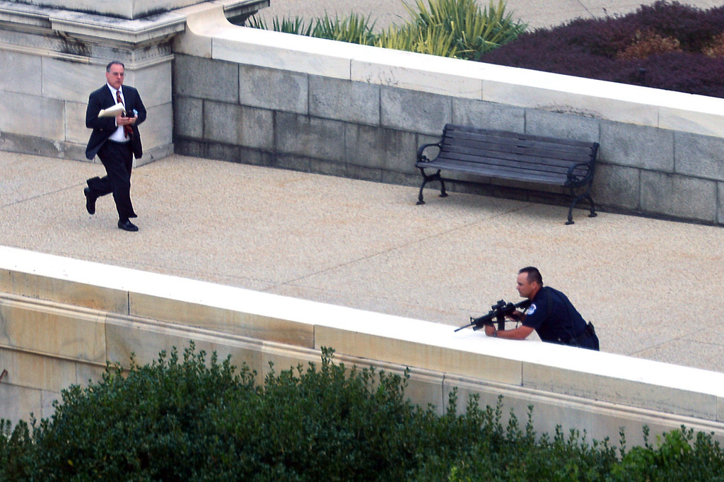 ". A man runs for cover as a police officer takes a shooting position at the site of a shooting October 3, 2013 on Capitol Hill in Washington, DC. The US Capitol was placed on security lockdown Thursday after shots were fired outside the complex, senators said. ""Shots fired outside the Capitol. We are in temporary lock down,\"" Senator Claire McCaskill said on Twitter. Police were seen running within the Capitol building and outside as vehicles swarmed to the scene. AFP PHOTO / Mandel NGAN/AFP/Getty Images"