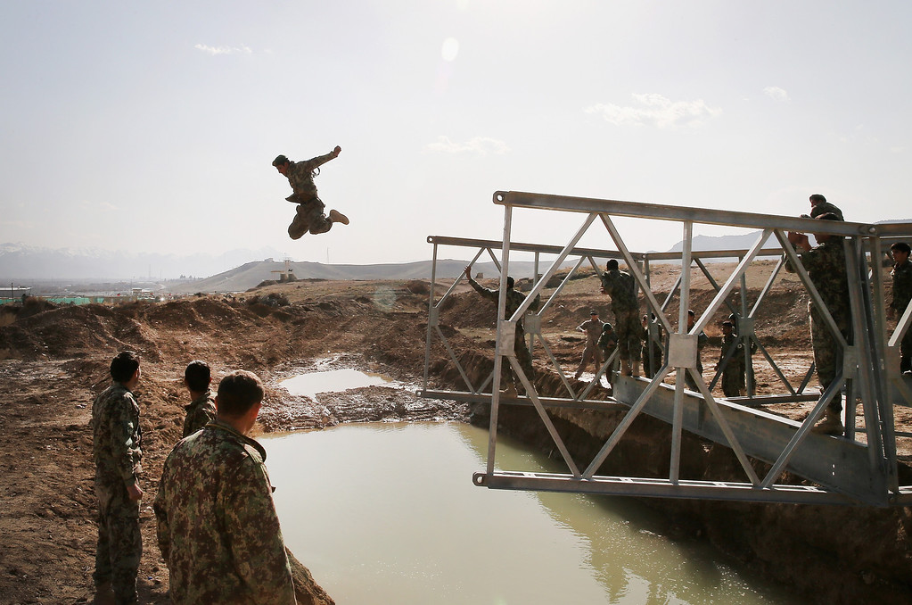 . KABUL, AFGHANISTAN - MARCH 18:  A soldier with the Afghan National Army\'s (ANA) National Engineer Brigade tries to make dry land after leaping from the top of a Mabey-Johnson portable pre-fabricated bridge which his unit was learning to construct with the help of U.S. Navy Seabees from Naval Mobile Construction Battalion (MCB) 28 at the ANA\'s combined Fielding Center on March 18, 2014 in Kabul, Afghanistan. The Seabees are attached to the U.S. Army\'s 130th Engineer Brigade are responsible for training ANA soldiers various engineering tasks at the facility. In a recent speech to his country\'s parliament, Afghan President Hamid Karzai said U.S. troops can leave Afghanistan at the end of the year because his military was ready to take over responsibility for the nation\'s security.  (Photo by Scott Olson/Getty Images) *** BESTPIX ***