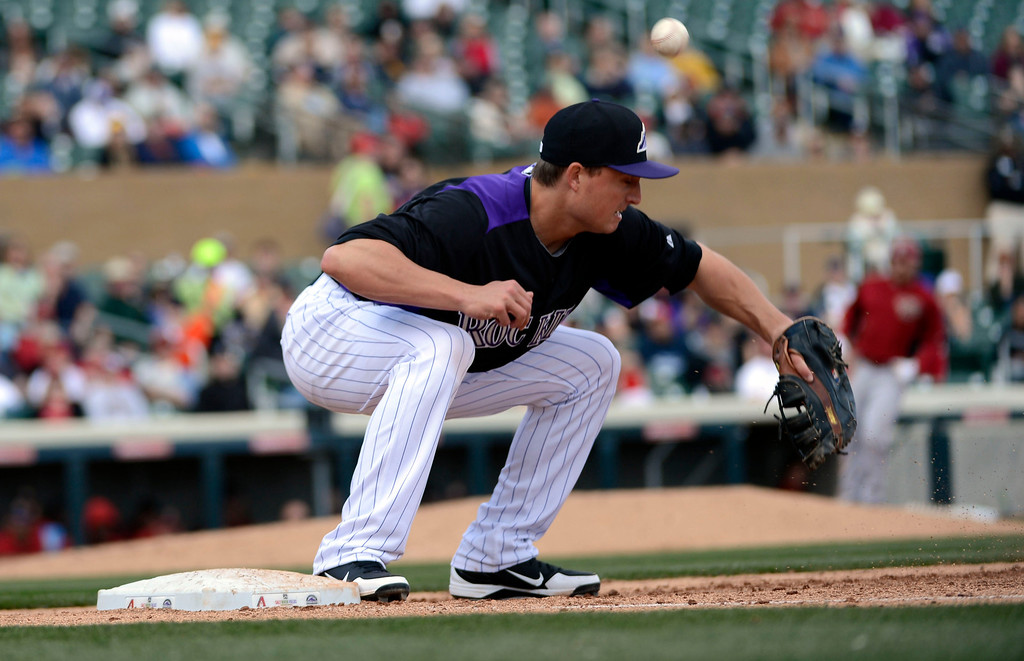 . SCOTTSDALE, AZ. - FEBRUARY 24: Jordan Pacheco (15) of the Colorado Rockies can\'t handle a throw from the out field as Eric Chavez (12) of the Arizona Diamondbacks was safe on the play in the fourth inning in their game February 24, 2013 in Scottsdale. (Photo By John Leyba/The Denver Post)