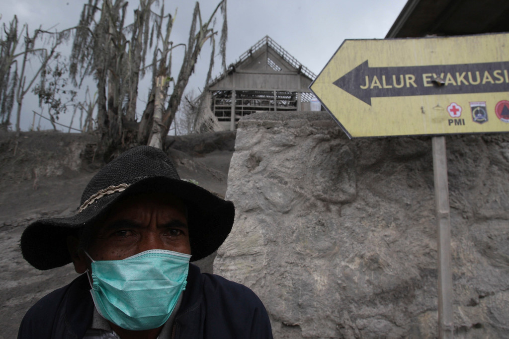 . A man waits for evacuation following an eruption of Mount Kelud, in Malang, East Java, Indonesia, Sunday, Feb. 16, 2014. (AP Photo/Trisnadi)