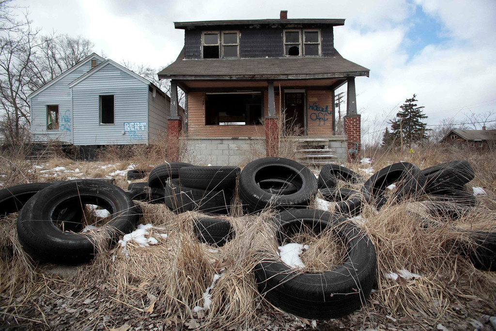 . Ilegally dumped tires sit in front of a vacant, blighted home in a once thriving neighborhood on the east side of Detroit, Michigan in this file photo taken March 20, 2013.   The city of Detroit is in final preparations to file for federal bankruptcy as early as Friday morning, the Detroit Free Press reported on Thursday, citing several unnamed sources. REUTERS/Rebecca Cook/Files