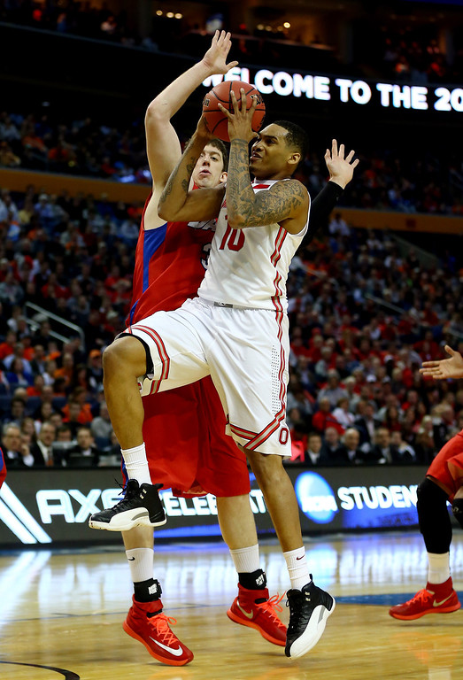 . LaQuinton Ross #10 of the Ohio State Buckeyes goes to the basket as Matt Kavanaugh #35 of the Dayton Flyers defends during the second round of the 2014 NCAA Men\'s Basketball Tournament at the First Niagara Center on March 20, 2014 in Buffalo, New York.  (Photo by Elsa/Getty Images)