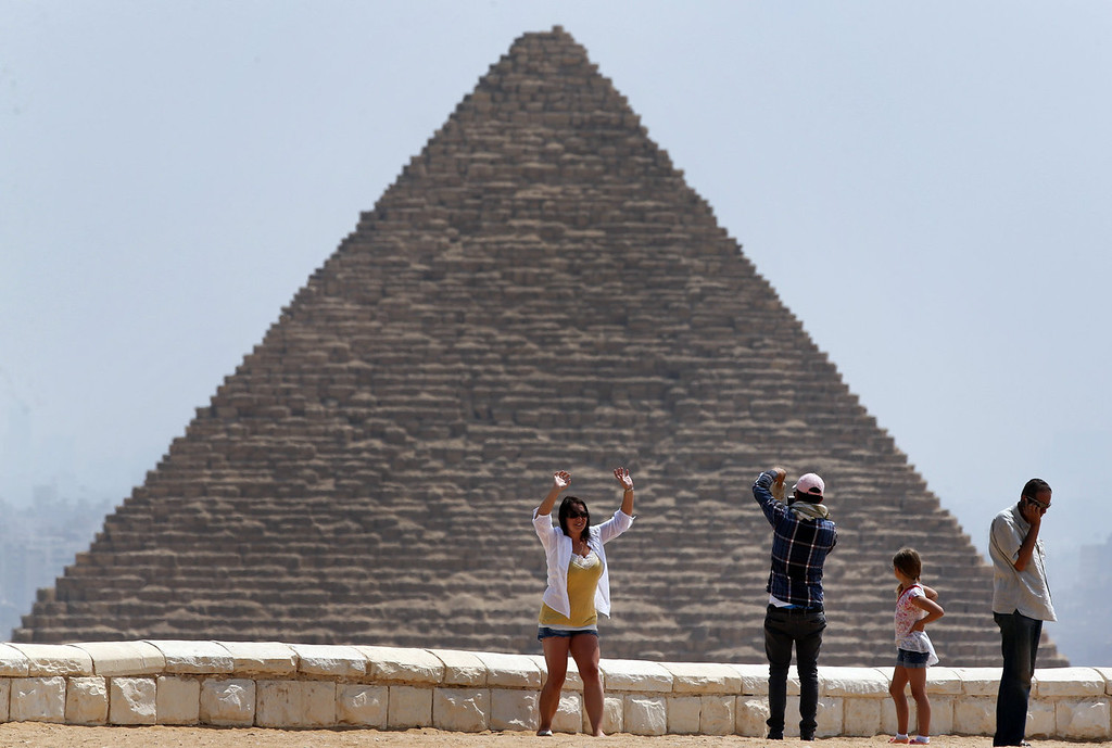 . A tourist poses for a photograph in front of Khufu, the largest of pyramids at the historical site of the Giza Pyramids, background, near Cairo, Egypt, Tuesday, Aug. 27, 2013.  The chairman of the Egyptian Airports Co. says some flights are arriving nearly empty to Egypt and that passenger traffic in the past week has fallen by half. Due to the country\'s violent turmoil, some flights that can carry more than 100 passengers from Europe arrive with just nine and return full from beach resorts. (AP Photo/Lefteris Pitarakis)