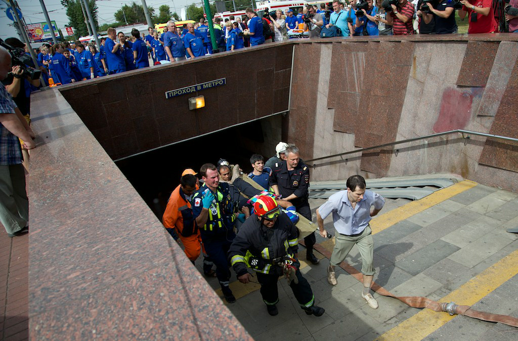 . Paramedics, a police officer and a volunteer carry an injured man out from a subway station after a rush-hour subway train derailment in Moscow, Russia, on Tuesday, July 15, 2014. (AP Photo/Ivan Sekretarev)