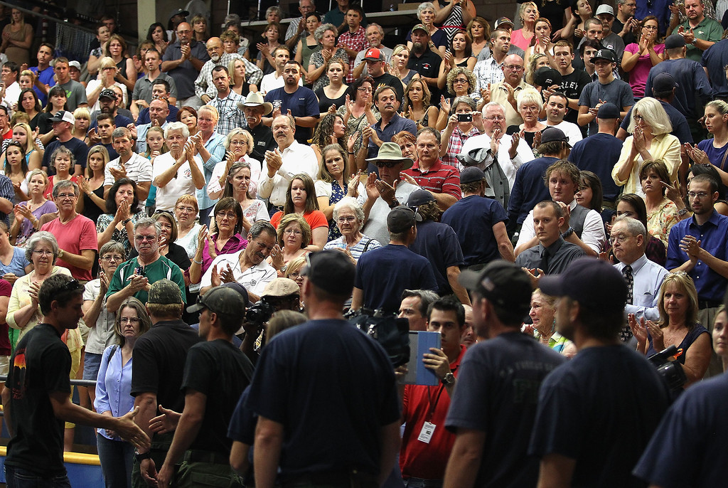 . Firefighters receive a standing ovation as they arrive at the memorial service at EmbryRiddle Aeronautical University on July 1, 2013 in Prescott, Arizona. On Sunday 19 Granite Mountain Interagency Hotshot Crew firefighters died battling a fast-moving wildfire near Yarnell, AZ.  (Photo by Christian Petersen/Getty Images)