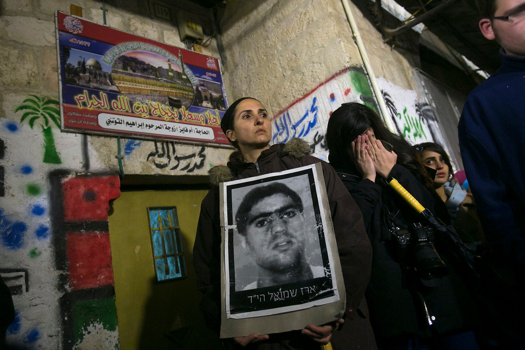 . Relatives of Israelis killed in attacks by Palestinian militants, hold photos of victims during a demonstration against the release of 26 long-serving Palestinian prisoners, in Jerusalem\'s old city, Monday, Dec. 30, 2013. Israel and the Palestinians are gearing up for the expected release by Israel of 26 of the longest-serving Palestinian prisoners. Israel has agreed to release the men, who were all convicted in deadly attacks of Israelis, as part of a U.S.-brokered package to restart peace talks. (AP Photo/Olivier Fitoussi)