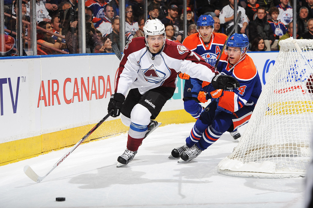. EDMONTON, CANADA - FEBRUARY 16: John Mitchell #7 of the Colorado Avalanche skates past the defence of Jordan Eberle #14 and Taylor Hall #4 of the Edmonton Oilers during the NHL game at Rexall Place on February 16, 2013 in Edmonton, Canada. (Photo by Derek Leung/Getty Images)