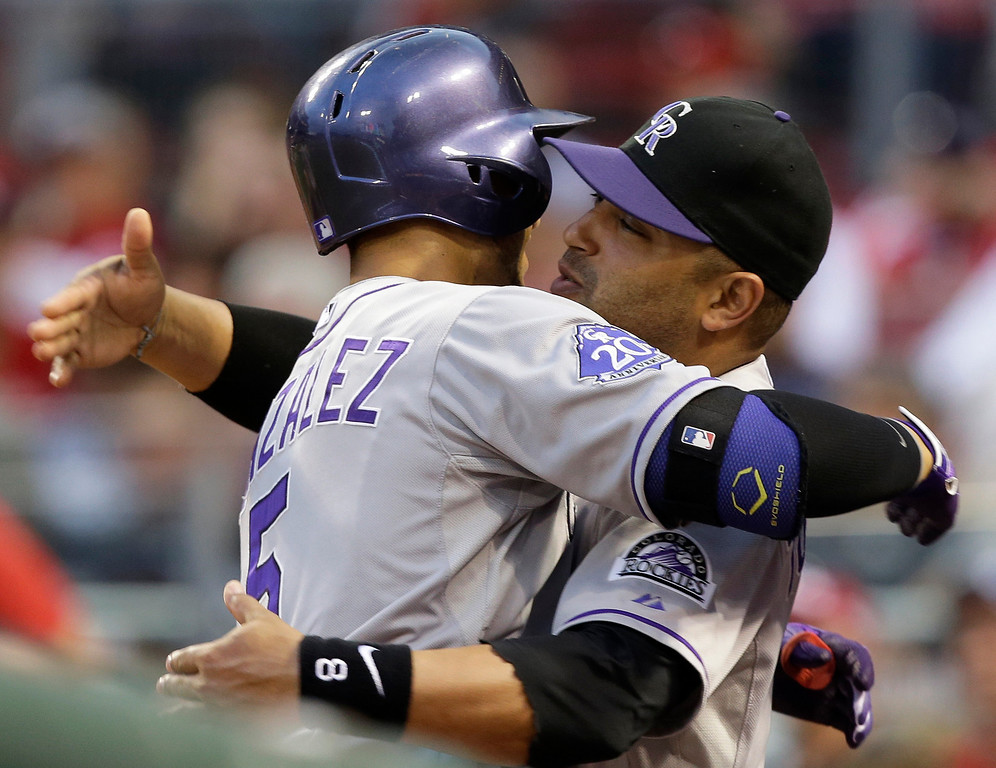 . Colorado Rockies\' Carlos Gonzalez (5) hugs Yorvit Torrealba after Gonzalez hit a three-run home run off Cincinnati Reds starting pitcher Pedro Villarreal in the fourth inning of a baseball game, Wednesday, June 5, 2013, in Cincinnati. (AP Photo/Al Behrman)