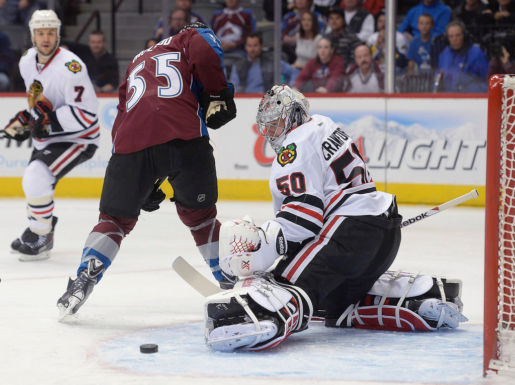 . Colorado Avalanche left wing Cody McLeod (55) tries to deflect the puck past Chicago Blackhawks goalie Corey Crawford (50) during the first period November 19, 2013 at Pepsi Center. (Photo by John Leyba/The Denver Post)