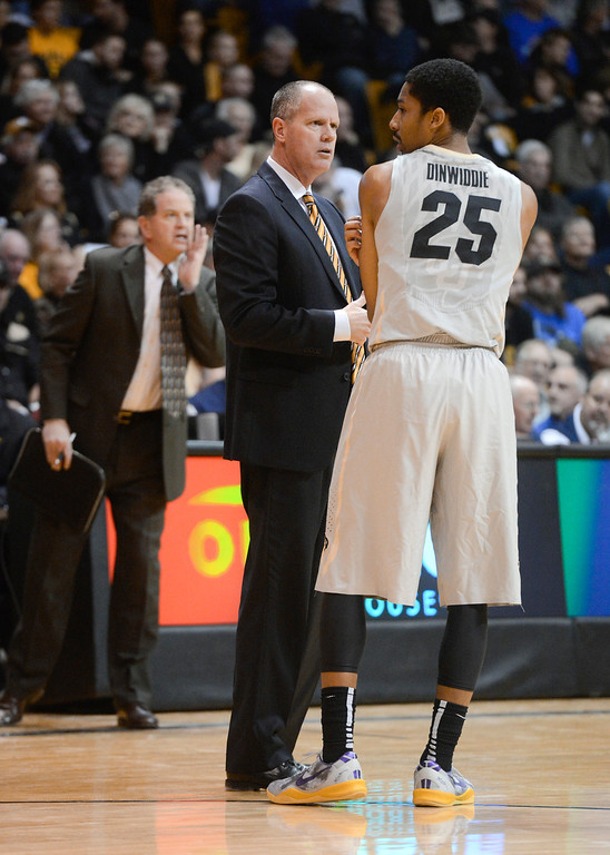 . Colorado University head coach, Tad Boyle, left, talks with point guard, Spencer Dinwiddie during the game against Kansas in the first half of play at the Coors Events Center in Boulder Colorado Saturday afternoon, December 07, 2013. Colorado stunned the Jayhawks 75-72. (Photo By Andy Cross/The Denver Post)