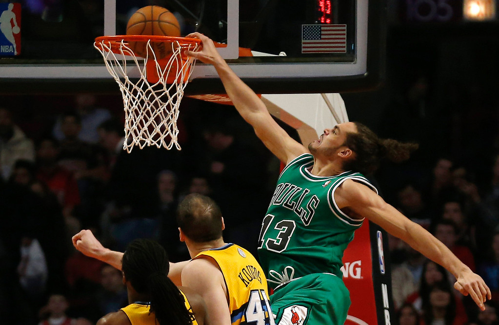 . Chicago Bulls\' Joakim Noah (R) dunks the ball over Denver Nuggets\' Kosta Koufos during the first half of their NBA basketball game in Chicago, Illinois March 18, 2013.  REUTERS/Jim Young