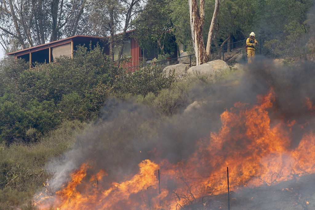 . Flames spread toward a house at the Cocos fire on May 15, 2014 in San Marcos, California. Fire agencies throughout the state are scrambling to prepare for what is expected to be a dangerous year of wildfires in this third year of extreme drought in California.   (Photo by David McNew/Getty Images)