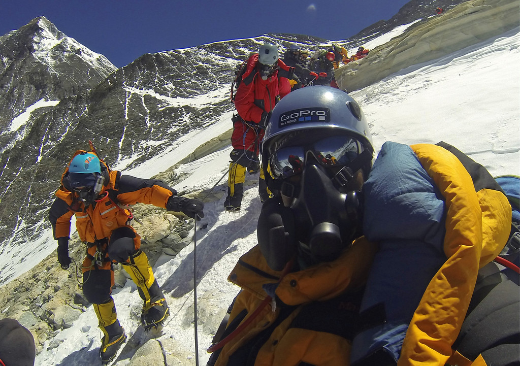 . In this Sunday May 19, 2013 photo, climbers are seen descending after scaling the 8,850-meter (29,035-foot) Mount Everest, peak seen on left. (AP Photo/ Pasang Geljen Sherpa)