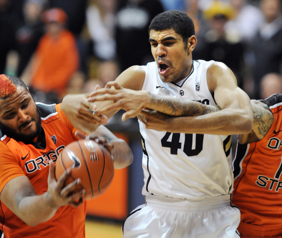 . Joe Burton, left, of Oregon State, and Josh Scott battle under the boards during the second half of the March 9, 2013 game in Boulder.    (Cliff Grassmick/Boulder Daily Camera)