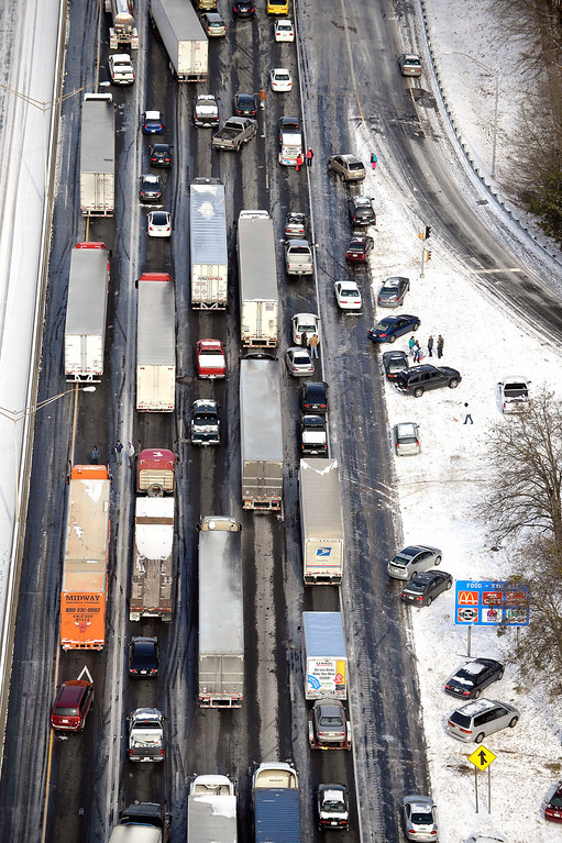 . In this aerial view looking at I-75 north at Moors Mill Rd., motorists get out of their vehicles to chat near abandoned cars along the ice-covered interstate after a winter snow storm , Wednesday, Jan. 29, 2014, in Atlanta. Georgia Gov. Nathan Deal said early Wednesday that the National Guard was sending military Humvees onto Atlanta\'s snarled freeway system in an attempt to move stranded school buses and get food and water to people. Georgia State Patrol troopers headed to schools where children were hunkered down early Wednesday after spending the night there, and transportation crews continued to treat roads and bring gas to motorists, Deal said.  (AP Photo/David Tulis)