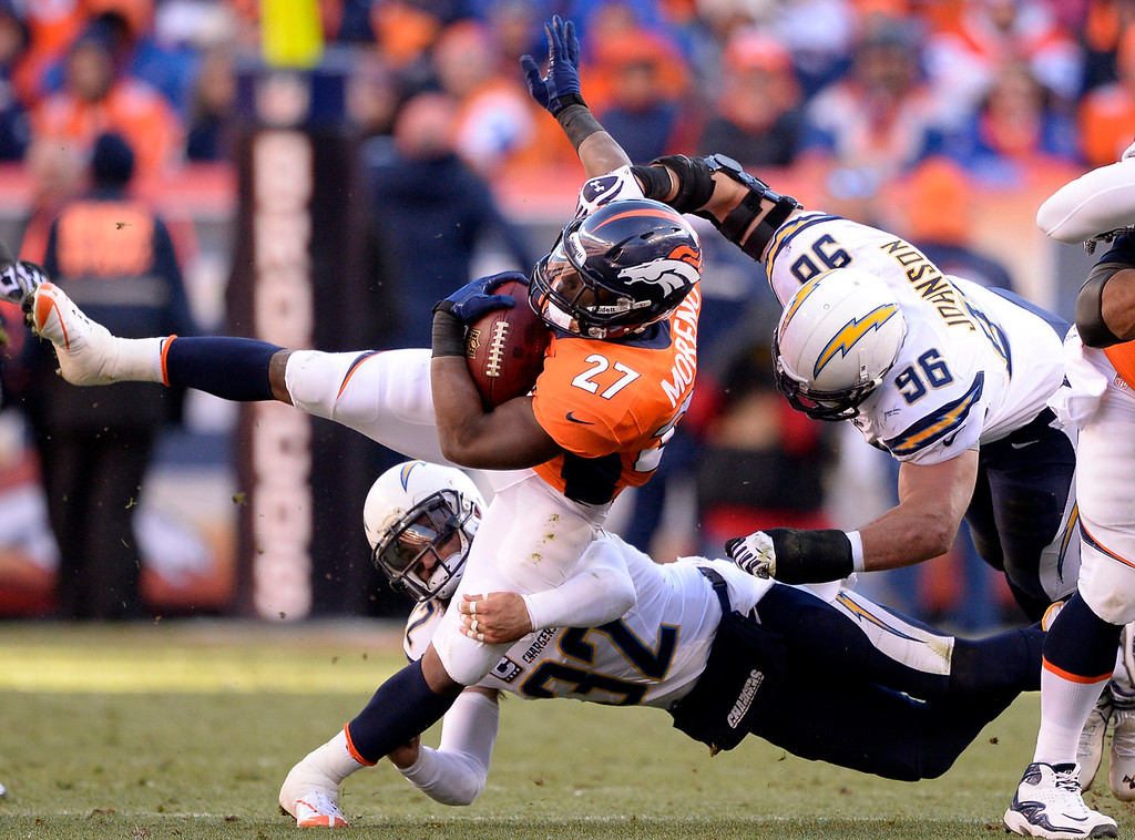 . Denver Broncos running back Knowshon Moreno (27) in the air for extra yards during the second quarter. The Denver Broncos vs. The San Diego Chargers in an AFC Divisional Playoff game at Sports Authority Field at Mile High in Denver on January 12, 2014. (Photo by John Leyba/The Denver Post)